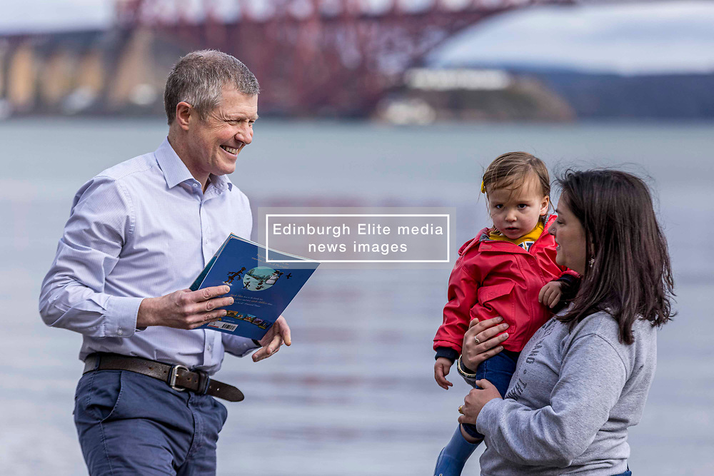 Scottish Liberal Democrats Teachers Announcement, Edinburgh, 25 March 2021 <br /> <br /> Pictured: Scottish Liberal Democrat Leader Willie Rennie announces plans for teachers as part of the 2021 Scottish Parliamentary election campaign.<br /> <br /> He is joined by Edinburgh Northern and Leith candidate, Rebecca Bell. Willie reads Rebecca's daughter, Daphne, a book on a giant beach chair with the view of the Forth Bridge behind.<br /> <br /> (c) Richard Dyson | EdinburghElitemedia.co.uk 2021