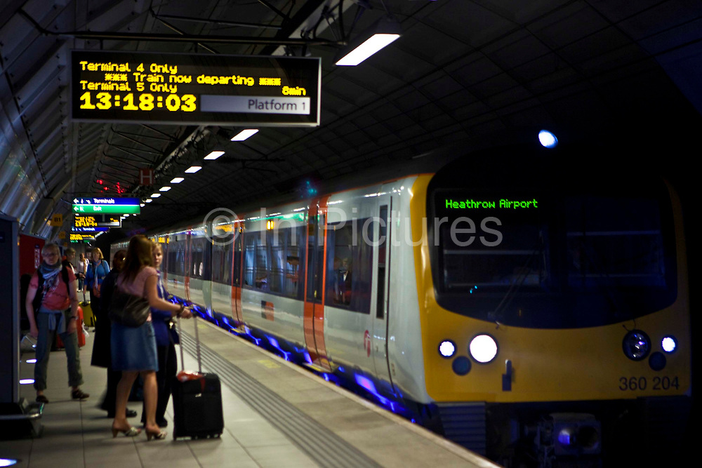 Passengers about to board the Heathrow Express train at London Heathrow Airport's Terminal 5 station.