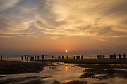 People walk in and along the shoreline of Laboni Beach, Cox Bazar, Chittagong Division, Bangladesh, Asia. The sun is setting behind clouds in the sky and the warm orange sunlight is reflected in the estuary water leading out to the sea.