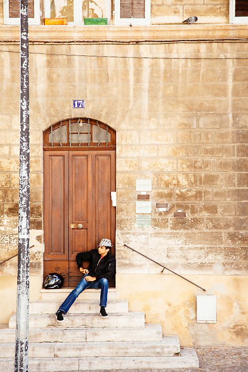 A young man sitting on the stairs in the Palais des Papes, Avignon.