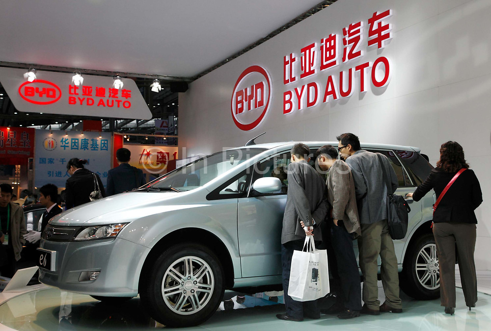 Visitors look at vehicles displayed by China's largest electric car maker BYD at a technology fair in Shenzhen, Guangdong Province, China on 17 November 2009. Headed by China's richest man along with a 232 million USD investment by Warren Buffett, BYD looks to expand its clout in the auto industry by announcing that it will spend roughly 200 million USD to build China's largest vehicle testing center.