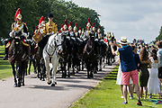 Members of the public watch the Household Cavalry Mounted Regiment proceed along the Long Walk for the ceremony of Trooping the Colour at Windsor Castle to mark the Queens official birthday on 12th June 2021 in Windsor, United Kingdom. A socially distanced and scaled down Trooping the Colour ceremony is taking place this year incorporating many of the elements from the annual ceremonial parade on Horse Guards, with F Company Scots Guards Trooping the Colour of the 2nd Battalion Scots Guards in the Castle Quadrangle.