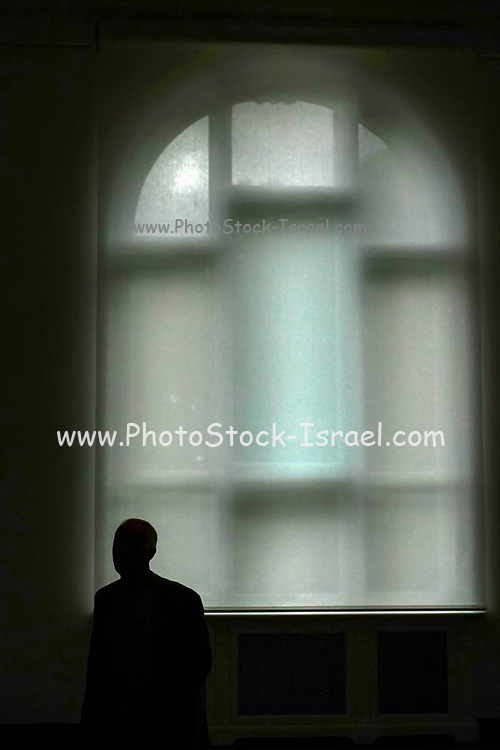 man silhouetted in front of a soft focus Large window