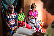 Berta Mapunda, back from left, Cosma Komba, and Wilfirda Ngonyani, listen as Gertruda Domayo reads from the bible in Nakahegwa, Tanzania. The group meet weekly to pray for one another and lend support. Sara A. Fajardo/Catholic Relief Services