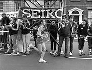 Finish of Dublin City Marathon .25/10/1982  Radio 2, Dublin City Marathon..1982.25.10.1982.10.25.1982.25th October 1982..The Radio 2 sponsored Dublin City Marathon finish at St Stephens Green Dublin..The overall winners were:Men, Gerry Kiernan,Listowel, Kerry. Women, Debbie Mueller,U.S.A. and the first wheelchair competitor Michael O'Rourke.A stopwatch check by an official as Debbie Mueller crosses the line.