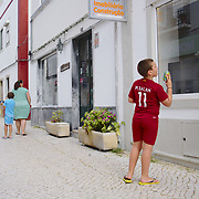 Boy wearing a Salah shirt staring at the signs at a shop.