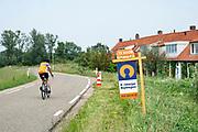 Nederland, Ooijpolder, 5-6-2019In de Ooijpolder staat aan de dijk een huis te koop . Het is een dijkhuis,dijkhuisje in een buurtschap wat de groenlanden heet . Een fietser, wielrenner , met een shirt van de Rabobank komt juist voorbij fietsen .Foto: Flip Franssen