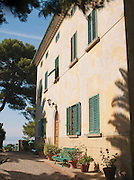 The facade of a large old villa, now the hotel Villa Bengodi on the coast of the Mediterranean Sea near Talamone, Tuscany, Italy