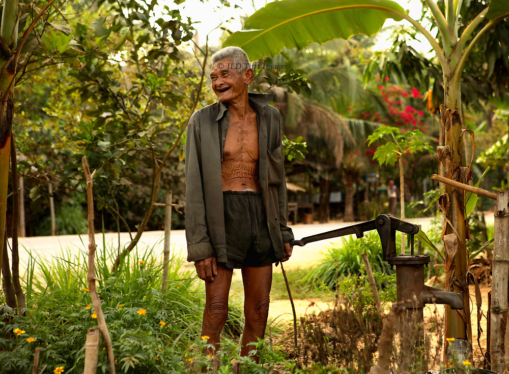Elderly Cambodian man pauses by an outdoor water pump in the town of Siem Reap, smiling cheerfully.  He says that he stayed alive by hiding in villages where nobody knew him.