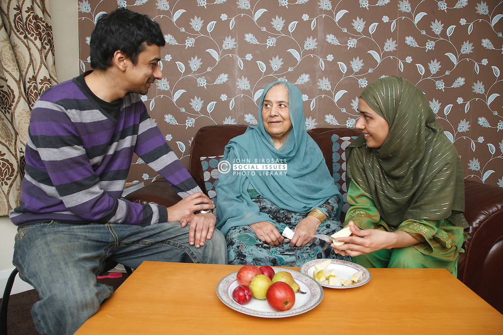 South Asian family relaxing, eating fruit.