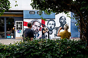 A courier delivers packages and onlookers admire the mural featuring England football manager Gareth Southgate, captain Harry Kane and Raheem Sterling in Vinegar Yard, Bermondsey. The mural urban street artists MurWalls was commissioned by Mayor Sadiq Khan to celebrate the England team reaching the final of Euro 2020, on 15th July 2021, in London, England.