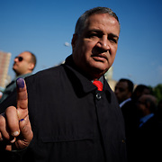 An egyptian man shows the ink in his finger after voting at El Tawfiya secondary school in Cairo's Shubra district.