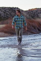 man walking through a stream