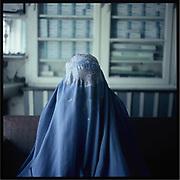 A woman in a burqa sits in a pharmacy in Kabul.