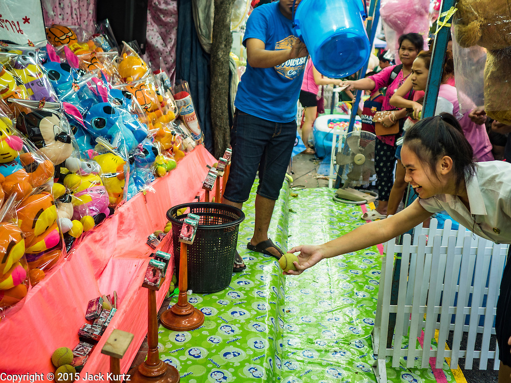 24 NOVEMBER 2015 - BANGKOK, THAILAND: A girl plays a midway ball game at the Wat Saket temple fair. Wat Saket is on a man-made hill in the historic section of Bangkok. The temple has golden spire that is 260 feet high which was the highest point in Bangkok for more than 100 years. The temple construction began in the 1800s in the reign of King Rama III and was completed in the reign of King Rama IV. The annual temple fair is held on the 12th lunar month, for nine days around the November full moon. During the fair a red cloth (reminiscent of a monk's robe) is placed around the Golden Mount while the temple grounds hosts Thai traditional theatre, food stalls and traditional shows.       PHOTO BY JACK KURTZ