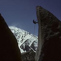 Climber rappels from boulder in Eastern Sierra Nevada, California.