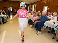 """The Friendship Club's Fashion Show features Carole Veer taking the runway in a wrap around skirt and a pretty loose """"tea"""" shirt.  Completing her outfit is a """"pill box"""" hat made popular by Jackie Kennedy during the 1960's.  (Karen Bobotas/for the Laconia Daily Sun)"""