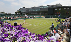 Spectators watch a match on court 14 on day three of the Wimbledon Championships at the All England Lawn Tennis and Croquet Club, Wimbledon.