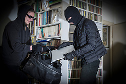 Burglars stealing laptop from living room of house