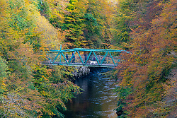 Visitors admiring view from footbridge with autumn colours on trees surrounding River Garry at Garry Bridge near Killiecrankie, Scotland, UK