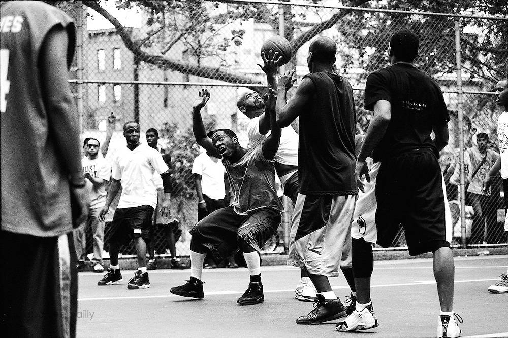 """May 4th 2010. New York, New York. United States..Located in the heart of Greenwich Village, the West 4th Street basketball Court, known as """"The Cage"""", offers no seating but attracts the best players and a lot of spectators as soon as spring is around the corner..Half the size of a regular basketball court, it creates a fast, high level of play. The more people watch, the more intense the games get. « The Cage » is a free show. Amazing actions, insults and fights sometimes, create tensions among and inside the teams. The strongest impose their rules. Charisma is present..""""The Cage"""" is a microcosm. It's a meeting point for the African American street culture of New York. Often originally from Jamaica or other islands of the Caribbean, they hang out, talk, joke, laugh, comment the game, smoke… Whether they play or not, they're here, inside """"The Cage"""". Everybody knows everybody, they all greet each other, they shake hands and hug: """"Yo, whasup man?"""""""