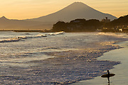 A surfer stands on a beach near Enoshima at dusk with Mount Fuji behind. Enoshima, Kanagawa, Japan. Monday October 23rd 2017
