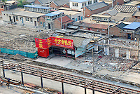 """China, Beijing, Chaoyang, San Jian Fang, 2008. A restaurant that has joined a business owner's protest using """"death"""" wreaths seems to be spared destruction for the moment. Superstition may have a role in explaining why it is still standing."""