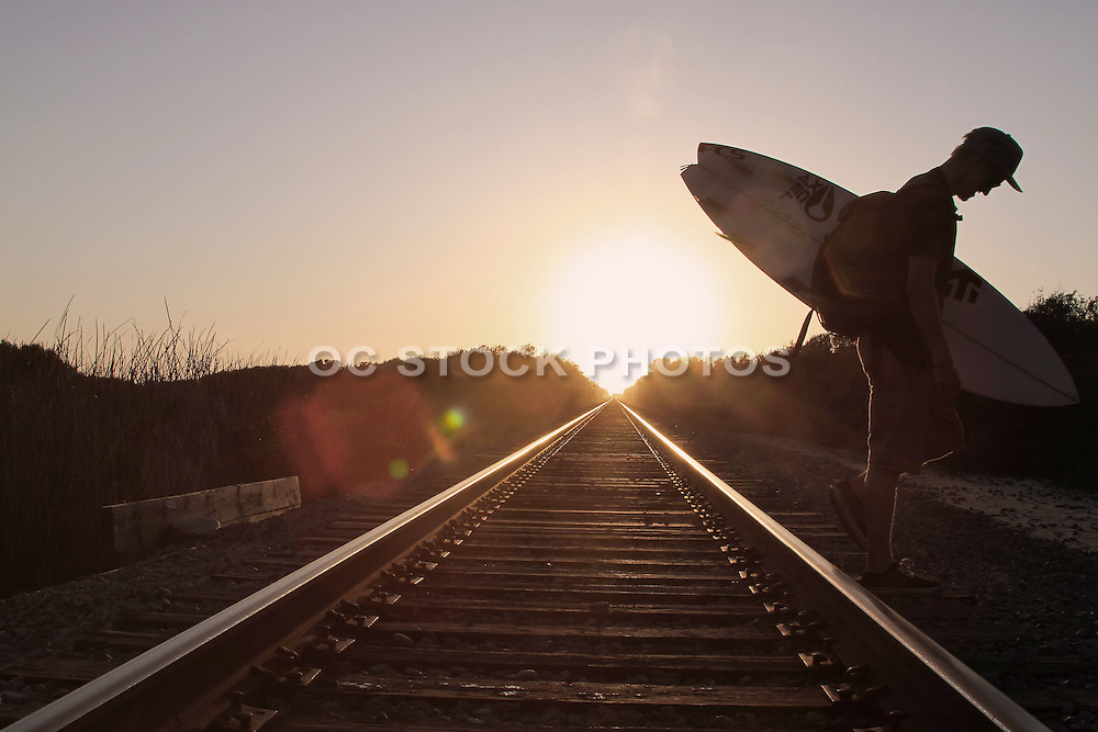 Surfer Crossing over Train Tracks at Sunset in San Clemente