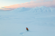 Mylène Jacquemart skis down Hallwylfjellet, Svalbard at sunset. Helvetiafjellet is visible across Adventdalen.