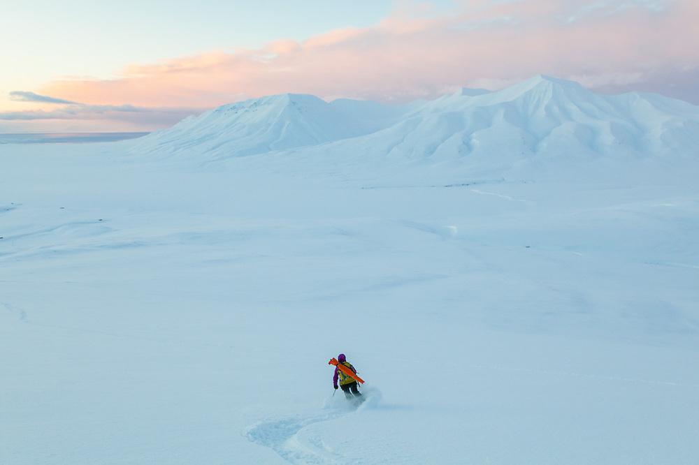 Mylène Jacquemart skis down Hallwylfjellet, Svalbard at sunset. Helvetiafjellet is visible across Adventdalen.