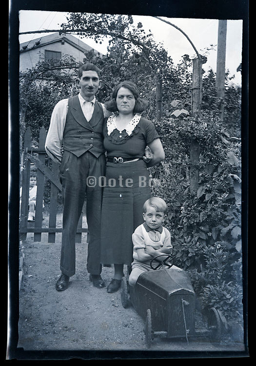 family portrait with child sitting in a toy automobile France ca 1930s