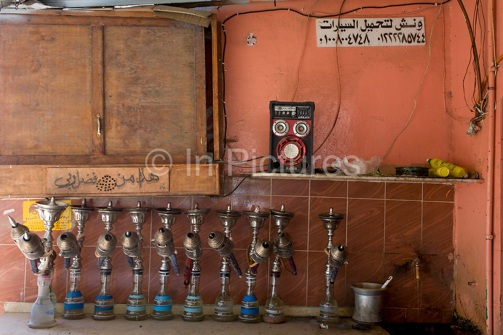 Hookahs (shisha) are kept on the table top of an street cafe in Kharga Oasis in the Western Desert, Egypt. A shisha or sheesha is from the Persian word shishe meaning glass and is the common term for the hookah in Egypt, Sudan and countries of the Arab Peninsula. A hookah is a single or multi-stemmed instrument for vaporizing and smoking flavored tobacco called shisha in which the vapor or smoke is passed through a water basin—often glass-based—before inhalation. Health risks of smoking hookah include exposure to toxic chemicals that are not filtered out by the water and risk of infectious disease when hookahs are shared.