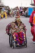A wheelchair bound reveler wears traditional Cajun Mardi Gras masks and costumes during the Courir de Mardi Gras chicken run on Fat Tuesday February 17, 2015 in Eunice, Louisiana. Cajun Mardi Gras involves costumed revelers competing to catch a live chicken as they move from house to house throughout the rural community.