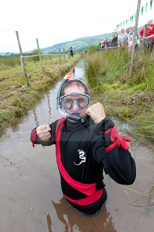 © Licensed to London News Pictures. 30/08/2015. Llanwrtyd Wells, Powys, Wales, UK. A participant dresses as a Kung-fu fighter. World Bogsnorkelling Championships, conceived 30 years ago in a Welsh pub by landlord Gordon Green, are held every August Bank Holiday at Waen Rhydd Bog. Using unconventional swimming strokes, participants swim two lengths of a 55 metre trench cut through a peat bog wearing snorkel and flippers. The world record was broken in 2014 by 33 year old Kirsty Johnson from Lightwater, Surrey, in a time of 1 min 22.56 secs. Photo credit: Graham M. Lawrence/LNP