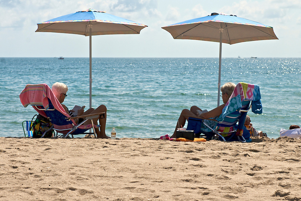 Mature womans relaxing and reading in the Beach. Fort Lauderdale, Florida.