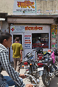 Street scenes of Meethapur slum, Delhi, India.  Motorbikes and bicycles parked outside an Operation Asha DOTS Centre where Tuberculosis patients attend everyday to collect and take their medication.