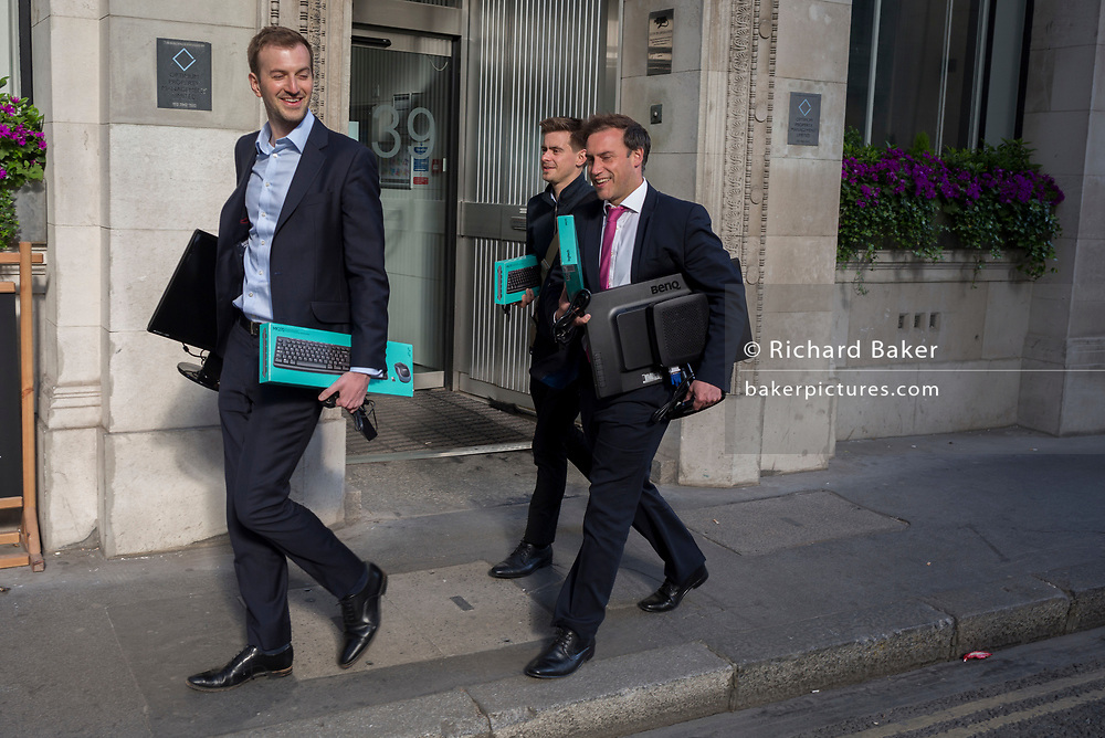 Three young men on Lime Street, carry the keyboards in the same packaging, on 10th May 2017, in the City of London, England.