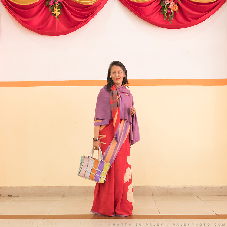 A woman wearing a Sari dress poses for a portrait during a wedding reception.