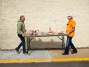 """11 MAY 2020 - DES MOINES, IOWA: RICHARD JESS, left, and LARRY CLAUSON move a table of donated baked goods into position for distribution at a """"no touch"""" emergency food pantry at DSM First Church in Des Moines. The emergency pantry at DSM First Church expanded from distribution one day a week to three days per week after the COVID-19 pandemic forced the closure of many Iowa businesses. Food banks and emergency pantries in Iowa continue to see increased demand for services, even though the governor is reopening the state's economy. Iowa's unemployment rate for April hasn't been released yet, but based on national trends, it is expected to soar to well over 10% from 3.8% in March. COVID-19 infections continue to skyrocket. On Monday, 11 May, the governor announced that 12,373 people tested positive for coronavirus (SAR-CoV-2) and  271 had died.           PHOTO BY JACK KURTZ"""