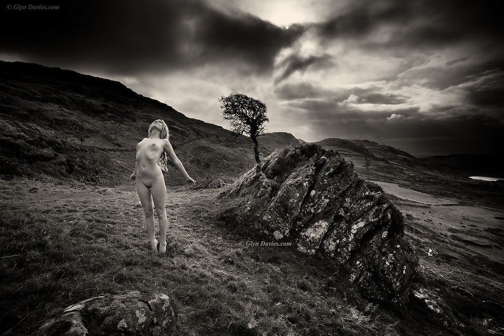 Nominated for 11th International B&W Spider Awards<br /> <br /> Innocence in a dark world where being nude outdoors is seen as sinful. That fact that she was conceived by two naked people; born into the world naked, from her mother's naked body seemed not to have a bearing on her freedom to enjoy this most natural state. As a young child she would run carefree on the open beach, delighting in not having to wear clothes. She saw other children happily playing naked there, equally without sin - just joyful, smiling and friendly - all enjoying an intimate natural connection to the amazing world that they had been introduced to.<br /> <br /> But as her body developed and her breasts grew, she was expected to cover up. The world now saw immorality in her naked maturity; her nudity became frowned upon; people couldn't bear to acknowledge her new sexuality or even gaze upon her natural form, fearful of their own sexual confusion and self-control. Her beautiful body must always be covered up, never revealed to others. The incredible and life affirming experience of being naked outdoors had become dirty and immoral – both her body and her real character were now hidden.<br /> <br /> Up here on a hillside however, a bright light appeared, slowly burning through the heavy clouds and she found herself nude. She felt the short grass beneath her feet and gentle sunshine on her back as she stretched her naked body once more, revealing herself completely to the earth, the sky and the elements. She stood on tiptoes, aching to be lifted upwards. She wanted to show the world that she was still alive, still innocent, even in her naked form. There was a discernible aura around this woman and I sensed her natural existence had just been spiritually validated.