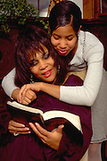 Mother age 45 reading the Bible to daughter age 15.  St Paul Minnesota USA