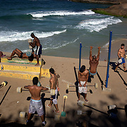 Fitness enthusiasts work out at an outdoor gymnasium overlooking the ocean at Parque do Arpoador, between the beaches of Ipanema and Copacabana, Rio de Janeiro,  Brazil. 6th July 2010. Photo Tim Clayton..The beaches of Rio de Janeiro, provide the ultimate playground for locals and tourists alike. Beach activity is in abundance as beach volley ball, football and a hybrid of the two, foot volley, are played day and night along the length and breadth of Rio's beaches. .Volleyball nets and football posts stretch along the cities coastline and are a hive of activity particularly at it's most famous beaches Copacabana and Ipanema. .The warm waters of the Atlantic Ocean provide the ideal conditions for a variety of water sports. Walkways along the edge of the beaches along with exercise stations and cycleways encourage sporting activity, even an outdoor gym is available at the Parque Do Arpoador overlooking the ocean. .On Sunday's the main roads along the beaches of Copacabana, Leblon and Ipanema are closed to traffic bringing out thousands of people of all ages to walk, run, jog, ride, skateboard and cycle more than 10 km of beachside roadway. .This sports mad city is about to become a worldwide sporting focus as they play host to the world's biggest sporting events with Brazil hosting the next Fifa World Cup in 2014 and Rio de Janeiro hosting the Olympic Games in 2016...