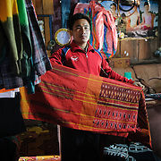 A salesman shows off a sample of his family's woven fabric in northeastern Laos.