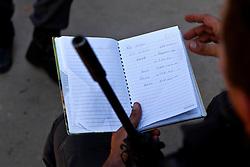 """Um policial do BOPE lê um """"livro caixa"""" com anotações sobre os faturamentos apreendida com  os traficantes na favela Morro do Alemão em 28 novembro de 2010 no Rio de Janeiro, Brasil. Após dias de preparação, forças de segurança do Brasil, lançaram um ataque contra uma favela, onde entre 500 e 600 traficantes de drogas estão escondidos e se recusam a se render. Cerca de 2.600 tropas aerotransportadas, marines e membros das unidades de elite da polícia faziam parte na operação como alvo um grupo de favelas sem lei, conhecido como Complexo de Alemào. A operação já matou 35 pessoas. FOTO: Jefferson Bernardes/Preview.com"""