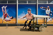 With images of Olympian athletes such as pole vaulter Polish Pawel Wojciechowski, American swimmer Michael Phelps and long Team GB jumper Phillips Idowu, workers push barrows of retail food outside the Olympic Megastore in the Olympic Park during the London 2012 Olympics. This land was transformed to become a 2.5 Sq Km sporting complex, once industrial businesses and now the venue of eight venues including the main arena, Aquatics Centre and Velodrome plus the athletes' Olympic Village. After the Olympics, the park is to be known as Queen Elizabeth Olympic Park.