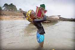 © Licensed to London News Pictures. 05/07/2013. Koulikoro,  Mali.  Fatumata (11) lifts a heavy bucket of sand onto her head in the river Niger.  She will spend 8 hours a day dredging sand which has been dropped by the workers.  The sand is transported to the shore which is then delivered across Mali for use within the construction industry.   Photo credit: Alison Baskerville/LNP
