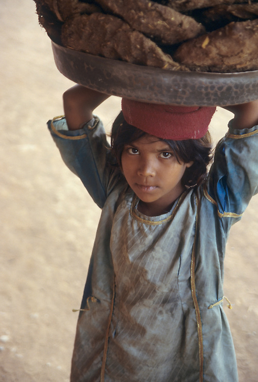 India, Rajasthan, Jaisalmer. Young girl holds bowls of dried cow dung (for fuel) on head