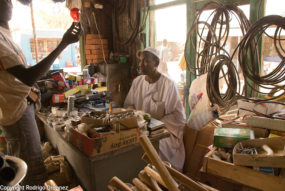 """Trader Mohammed Abdulrahman, from El Muglad (right), sells a light bulb to a customer at his hardware store in the market of Abyei. Recent developments in Abyei town are making people settle down. """"No one was thinking of using these materials before."""""""