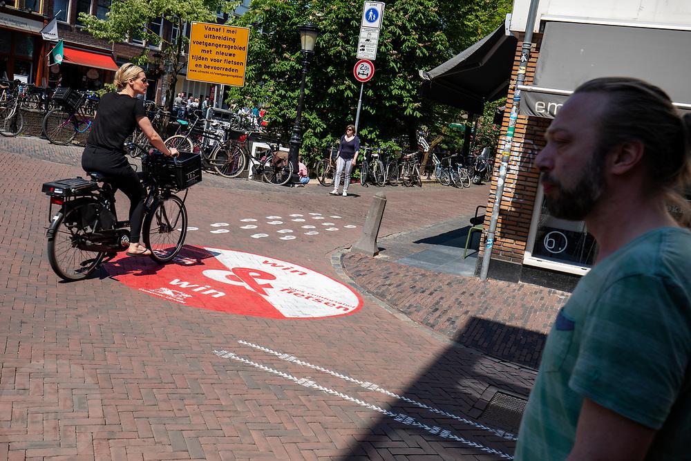 Een vrouw fietst door waar het voetgangersgebied begint. In Utrecht worden fietsers gewezen op een andere route. Vanaf 1 mei mogen fietsers gedurende het grootste deel van de dag niet meer door een deel van het centrum fietsen. Het voetgangersgebied is fors uitgebreid.<br /> <br /> A big painted sign on the road suggest cyclists another route to ride at the city center in Utrecht. A part of the center is closed for cyclists for the main part of the day.