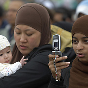 Young muslim women and baby girl wearing hijab and taking pictures  with mobile phone , Eid in the Square, London, England<br />